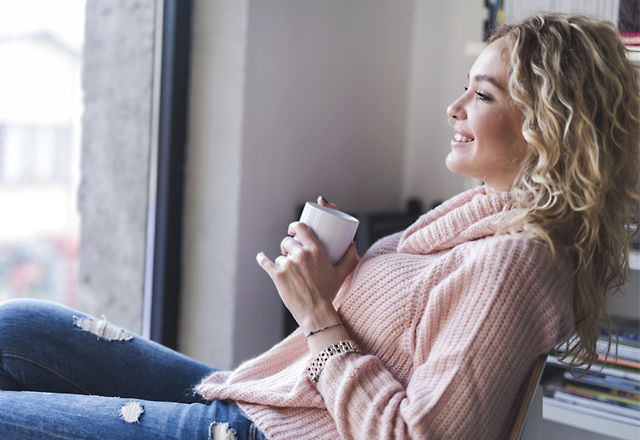Woman relaxing while drinking coffee and looking through window.